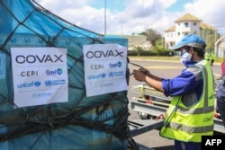 FILE - A worker handles boxes of COVID-19 vaccines, delivered as part of the COVAX equitable vaccince distribution program, at Ivato International Airport, in Antananarivo, Madagascar, May 8, 2021.