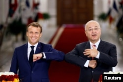 French President Emmanuel Macron and Iraq's President Barham Salih greet each other with an elbow bump as they attend a news conference in Baghdad, Iraq, Sept. 2, 2020.