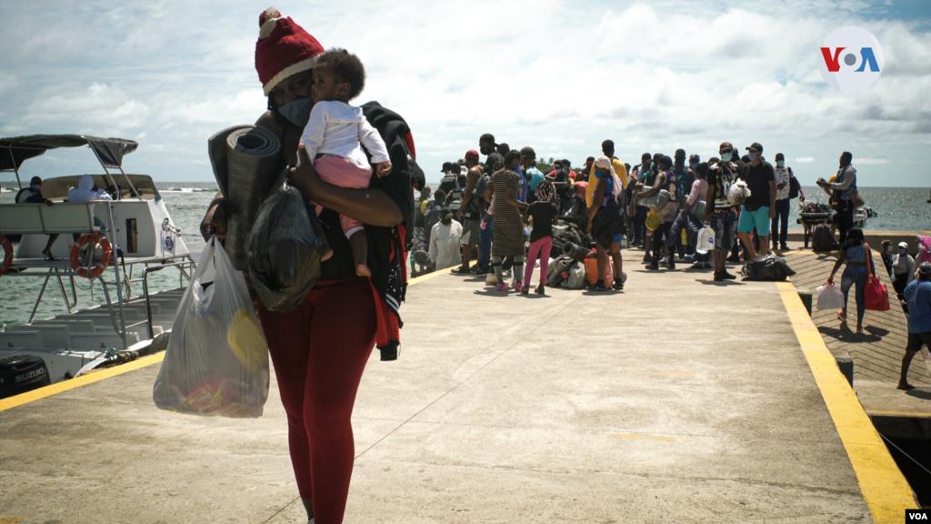 Equipados con tiendas de campaña, colchonetas, plásticos para la lluvia, entre otros enseres, los migrantes arriban al muelle de Capurganá en la frontera con Panamá.