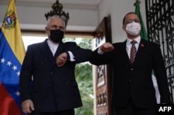 El canciller de la República Islámica de Irán, Javad Zarif, izquierda, choca con el canciller venezolano Jorge Arreaza en el palacio Casa Amarilla en Caracas.