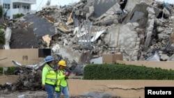 Rescatistas caminan entre los escombros después de la demolición controlada de la parte restante del complejo Champlain Towers South mientras continúan los esfuerzos de búsqueda y rescate en Surfside, Florida, el 6 de julio de 2021.