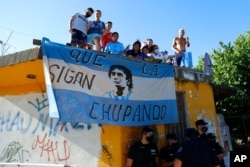 អ្នកគាំទ្រកីឡាករបាល់ទាត់លោក Diego Maradona ឈរនៅលើដំបូលផ្ទះខណៈក្បួនម៉ូតូដង្ហែសព្វលោកនៅក្នុងរដ្ឋធានីប៊ុយណូស៊ែ ប្រទេសអាហ្សង់ទីន កាលពីថ្ងៃទី២៦ ខែវិច្ឆិកា ឆ្នាំ២០២០។ (AP)