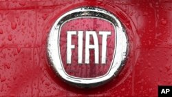 FILE - In this Jan. 2, 2014 file photo, a Fiat logo pictured on a car in Milan, Italy. Italian-American carmaker Fiat Chrysler Automobiles on Oct. 30, 2019, confirmed that it is in talks with French rival PSA Peugeot.