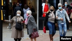 People wearing protective masks wait to cross the road, as the coronavirus disease (COVID-19) outbreak continues, in Manchester, Britain, Oct. 19, 2020.
