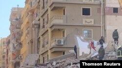 Pessoas procuram por sobreviventes perto do prédio que colapsou em Gesr al-Suez, Cairo
