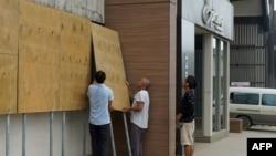 当地人在热带龙卷风哈罗德登录瓦努阿图首都维拉港前在商店门口假设防护板。(2020年4月6日)