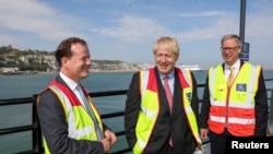 ສະມາຊິກສະພາອັງກິດ ທ່ານ Charlie Elphicke (ຊ້າຍ)  ໂອ້ລົມກັບ ທ່ານ Boris Johnson (ກາງ) ແລະທ່ານ Doug Bannister, ປະທານຜູ້ບໍລິຫານຂອງບໍລິສັດ Port of Dover Ltd., ໃນການໂຄສະນາຫາສຽງ ເມືອງ Dover, ອັງກິດ, 11 ກໍລະກົດ 2019.