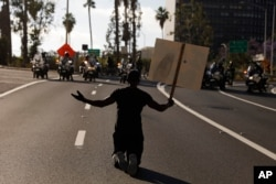 """A man kneels on the street in front of police officers while chanting """"I can't breathe"""" during a protest over the death of George Floyd, May 29, 2020, in Los Angeles. Floyd died Memorial Day while in police custody in Minneapolis."""