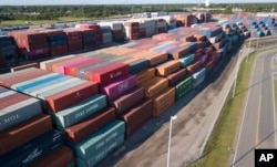 FILE - China Shipping Company and other containers are stacked at the Virginia International's terminal in Portsmouth, Va., May 10, 2019.