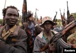 FILE - SPLA-IO rebels hold up guns in Yondu, South Sudan, Aug. 25, 2017.