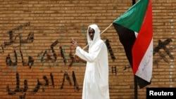 Sudan bayrog'ini ko'tarib olgan namoyishchi, Xartum, Sudan, 2019-yil, 19-aprel