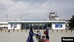 FILE - Afghan passengers walk in front of Hamid Karzai International Airport in Kabul, Afghanistan, March 29, 2016.