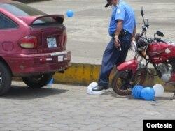Un policía revienta globos usados en una conmemoración de familiares de manifestantes en el aniversario del inicio de la crisis política en Nicaragua de 2018, en Masaya el 20 de abril de 2020. Foto cortesía de Noel Miranda.
