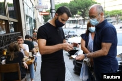 Restaurant staff checks a digital vaccination certificate at the entrance, on the day that Portugal's government imposed stricter rules in an attempt to bring under control a surge of COVID-19 cases, in Porto, Portugal, July 10, 2021.