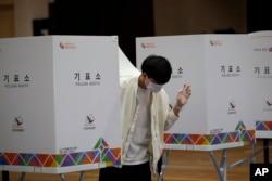 Seorang pemilih yang mengenakan masker keluar dari bilik suara di sebuah TPS di Seoul, Selasa (15/4).