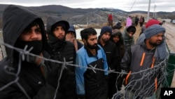 Migrants watch Bosnian soldiers put up tents at the Lipa camp outside Bihac, Bosnia, Jan. 1, 2021. Hundreds of migrants have been stuck in a burned-out camp in the northwest of the country in winter weather and with no facilities.