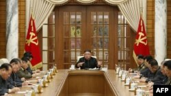 This picture taken on November 29, 2020 and released from North Korea's official Korean Central News Agency (KCNA) on November 30, 2020 shows North Korean leader Kim Jong Un (C) attending a meeting of the 21st Political Bureau of the 7th Central…