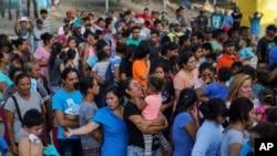 """Sèvis Imigrasyon Ameriken te voye pi fò nan imigran sa yo o Meksik nan kad aplikasyon politik administrasyon Trump la te adopte e ki rele """"Rete tann o Meksik"""". Yo te mete yo sou liyn pou yo te jwenn manje nan yon kan sou Pon Gateway International nan vil Matamoros, o Meksik. (Dat: 30 out 2019)."""