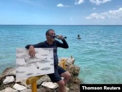 Cuban artist Sandor Gonzalez speaks to the media after painting underwater in Punta Perdiz, June 18, 2019