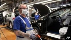 Un empleado se encuentra cerca de vehículos en producción con una máscara facial en la planta de VW en Wolfsburg, Alemania. Volkswagen está lanzando gradualmente la producción en plantas importantes después del cierre de la corona.