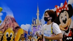 A woman in Tokyo wears a protective mask as she passes Tokyo Disneyland.