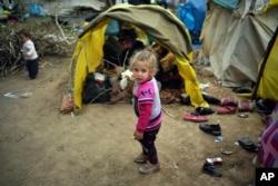 A child walks next to tents in a migrant camp set up near the Turkish-Greek border in Pazarkule, Edirne region, Turkey, March 10, 2020.