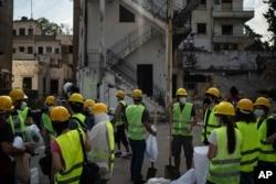 بیروت کے دھماکے سے تباہ ہونے و الی ایک عمارت میں پھینس جانے والے افراد کو نکالا جا رہا ہے۔