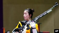 Yang Qian, of China, reacts after winning the gold medal in the women's 10-meter air rifle at the Asaka Shooting Range in the 2020 Summer Olympics, July 24, 2021, in Tokyo, Japan.