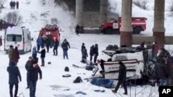 This handout photo provided by Russia Emergency Situations Ministry press service shows Emergency Situations employees and police working at the side of the bus after plunging from a bridge over the Kuenga River, about 4900 kilometers (3100 miles)…