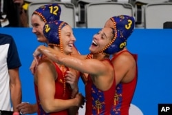 Spain's Marta Bach (2) and Pili Pena (8) celebrate after a win over South Africa in a preliminary round women's water polo match at the 2020 Summer Olympics, July 24, 2021, in Tokyo, Japan.