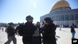 Polisi Israel menahan seorang warga Palestina di komplek masjid al-Aqsa di Yerusalem, pada perayaan hari raya Idul Adha di sana, Minggu (11/8).(AP Photo/Mahmoud Illean)