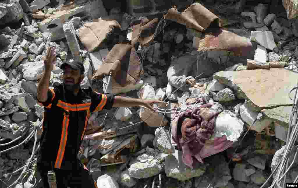 Un trabajador de rescate palestino gesticula junto a una víctima entre los escombros en el lugar de los ataques aéreos israelíes, en la ciudad de Gaza.
