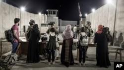 美国海军陆战队公布的照片显示,美国陆军第82空降师的军人在喀布尔哈米德·卡尔扎伊国际机场检查被撤离人员。(2021年8月25日)