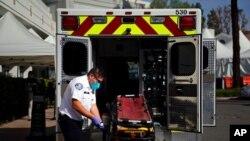 Petugas mendisinfeksi brankar setelah mengangkut seorang pasien di Rumah Sakit St. Joseph di Orange, California, 7 Januari 2021. (Foto: AP).