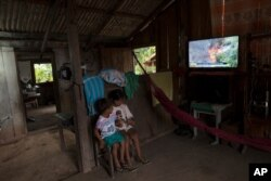 Children play with a cell phone as a television news airs in the background in the Cajueiro village, Para state, Brazil, Sept. 3, 2019.