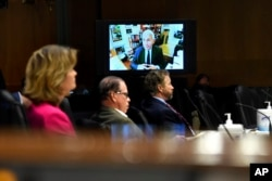 Senators listen as Dr. Anthony Fauci, director of the National Institute of Allergy and Infectious Diseases, speaks remotely during a virtual Senate Committee for Health, Education, Labor, and Pensions hearing on Capitol Hill, May 12, 2020.