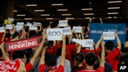 "FILE - Hong Kong soccer fans turn their backs and boo the Chinese national anthem as they chant ""Hong Kong is not China"" during a World Cup qualifying soccer match between Hong Kong and Iran, in Hong Kong, Sept. 10, 2019."
