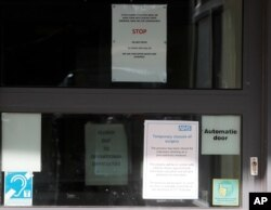 Signs at the entrance of the County Oak Medical Centre GP practice in Brighton, England, Feb. 11, 2020. The center has been temporarily closed following reports a member of staff there was one of those infected with coronavirus.