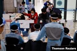 28일 한국 인천공항에서 방역 관계자들이 입국자들을 대상으로 신종 코로나바이러스 방역 절차를 진행하고 있다.