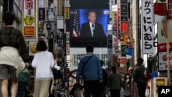 A screen shows a broadcast of President-elect Joe Biden speaking, Nov. 8, 2020, at the Shinjuku shopping district in Tokyo, Japan.