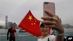 FILE - Pro-China supporters take a selfie with a Chinese national flag during a rally in Hong Kong, Aug. 17, 2019. Twitter has suspended accounts that it believes were part of a Chinese government campaign targeting the protest movement in Hong Kong.