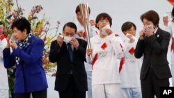 Tokyo Gov. Yuriko Koike, left, Tokyo 2020 Organizing Committee President Seiko Hashimoto, right, and attendees take off their face masks while preparing to pose for group photos during the Tokyo 2020 Olympic Torch Relay Grand Start.
