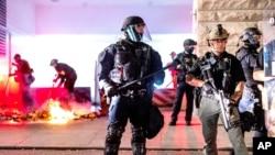 پورٹ لینڈ میں سیکیورٹی اہل کار کورٹ ہاؤس کے باہر لگائی جانے والی آگ بجھا رہے ہیں۔ 2 اگست 2020