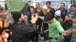 Syrian, Afghan refugees dance outside Vienna, Austria train station, Sept. 15, 2015.
