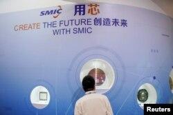 រូបឯកសារ៖ បុរសម្នាក់ឈរមុខកន្លែងតាំងពិព័រណ៍ផលិតផលបន្ទះឈីបរបស់ក្រុមហ៊ុនSemiconductor Manufacturing International Corporation (SMIC) នៅក្នុងកម្មវិធីពិព័រណ៍បន្ទះឈីបអន្តរជាតិ ក្នុងទីក្រុងសៀងហៃ ប្រទេសចិន កាលពីថ្ងៃទី១៤ ខែតុលា ឆ្នាំ២០២០។