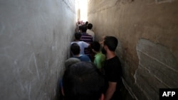 FILE - Syrians line up to buy bread at a shop in the town of Binnish in the country's northwestern Idlib province, June 9, 2020.