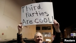 FILE - Libertarian Jeff Jared of Kirkland, Washington, holds a sign in support of third parties in Seattle, Jan. 31, 2019.