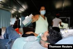 Una mujer muestra el empaque de una mascarilla a un paciente que padece COVID-19, mientras este recibe una máscara de oxígeno, en la carpa médica en el Poliedro de Caracas, el 21 de marzo de 2021.