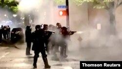 Polisi mengarahkan senjata mereka ke arah pengunjuk rasa yang berdemonstrasi di Portland, Oregon. (Foto: dok).