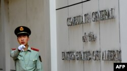 (FILES) This file photo taken on September 18, 2012 shows a Chinese paramilitary policeman gesturing to photographers at the entrance to the US consulate in Chengdu, southwest China's Sichuan province. - China said on July 24, 2020 it had revoked…